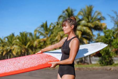 tanned surfer in swimsuit posing with surfboard on tropical beach
