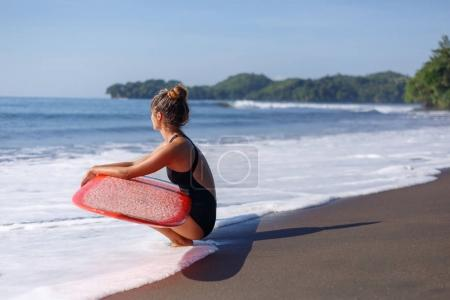 young surfer in swimsuit sitting with red surfboard near the sea
