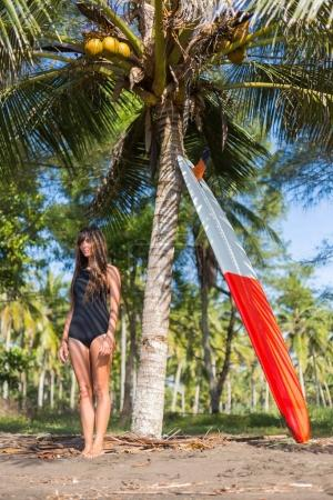 tanned girl in black swimsuit standing near palm with surfboard