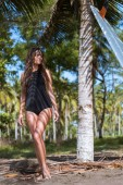 beautiful slim girl in swimsuit posing with surfboard near palm tree