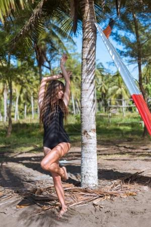 attractive girl with long hair in black swimsuit posing with surfboard near palm tree