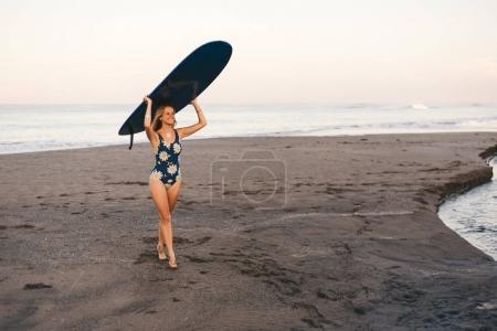 Foto de Joven deportista en natación traje llevar tablero que practica surf azul en la cabeza en la costa - Imagen libre de derechos