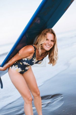 portrait of cheerful sportswoman in swimming suit with blue surfing board on back on beach
