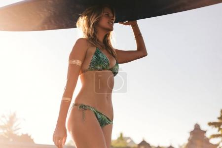 low angle view of young sportswoman in bikini carrying surfing board on head on beach
