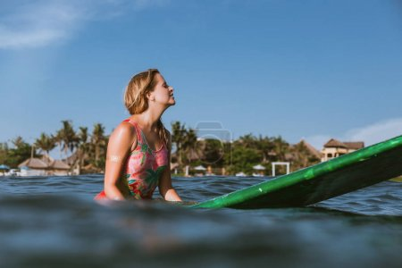 side view of young woman in swimming suit resting on surfing board in ocean with coastline on background