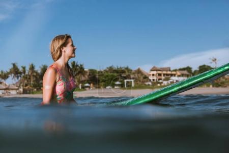 Photo pour Vue latérale d'une jeune femme séduisante en maillot de bain reposant sur planche de surf dans l'océan avec littoral sur fond - image libre de droit
