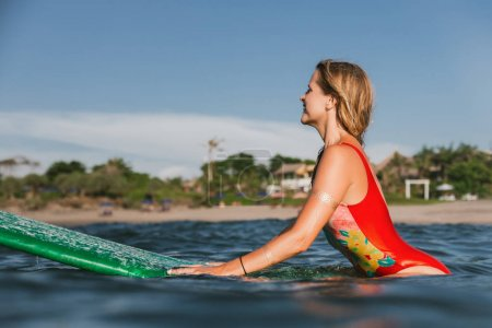side view of young attractive woman in swimming suit resting on surfing board in ocean with coastline on background