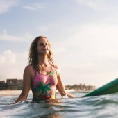 portrait of young woman in swimming suit resting on surfing board in ocean