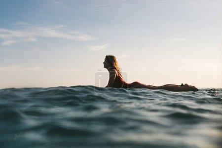 Photo pour Vue latérale de la femme en costume surf seul la natation dans l'océan - image libre de droit