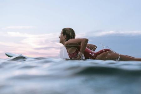 side view of sportswoman in swimming suit surfing alone in ocean