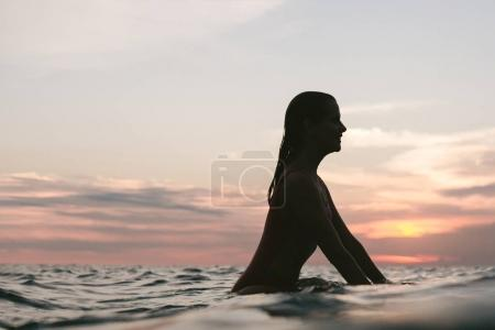 side view of silhouette of woman resting on surfing board in ocean on sunset