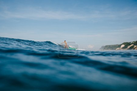 handsome man having fun on surfboard while having vacation