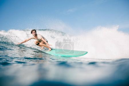 handsome man in wet t-shirt riding waves on surfboard while having vacation