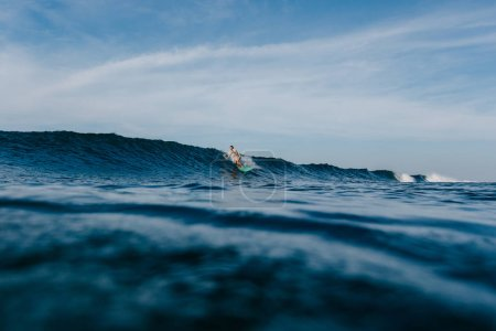 Foto de Handsome man in wet t-shirt riding waves on surfboard on sunny day - Imagen libre de derechos