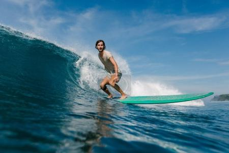 young man in wet t-shirt riding waves on surfboard on sunny day