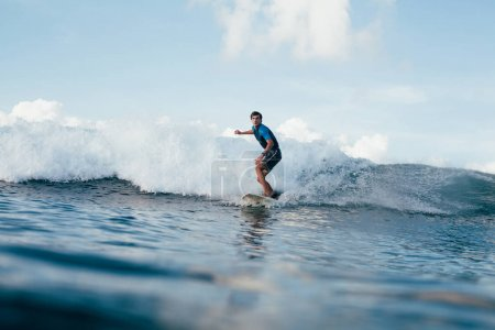 handsome young man in wetsuit surfing on sunny day