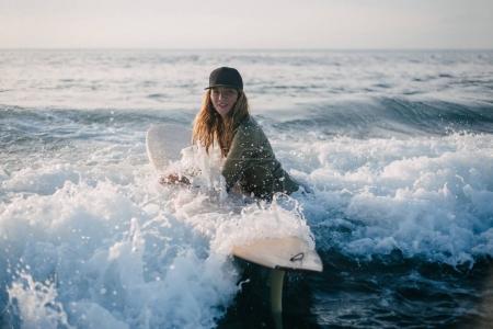 Photo pour Jeune femme en combinaison avec planche de surf entrant dans l'océan le soir - image libre de droit