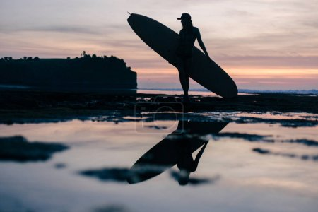 Photo for Silhouette of young woman with surfboard on seashore in evening - Royalty Free Image
