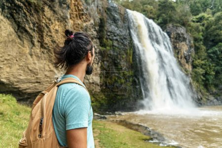 Photo for Young bearded man looking at waterfall, Hunua Falls, New Zealand - Royalty Free Image