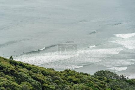 Photo for Aerial view of wavy ocean and green hill, Muriwai beach, New Zealand - Royalty Free Image
