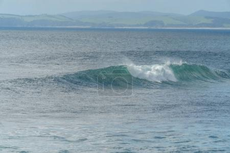 Photo pour Prise de vue spectaculaire de l'océan ondulé avec des montagnes au loin, plage de Leigh, Nouvelle-Zélande - image libre de droit