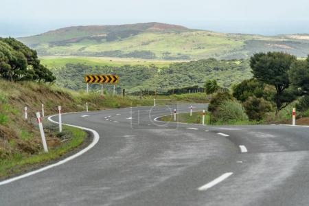 Foto de Empty mountain road with turn right sign board and green hills on background, New Zealand - Imagen libre de derechos