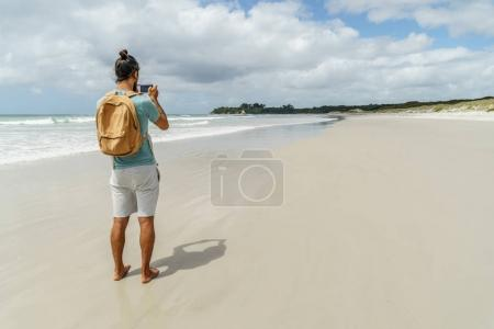Photo for Rear view of man taking photo of coastline with smartphone, Rarawa beach, New Zealand - Royalty Free Image