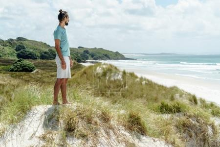 Photo for Lonely thoughtful man standing on seashore and looking at sea, Rarawa beach, New Zealand - Royalty Free Image