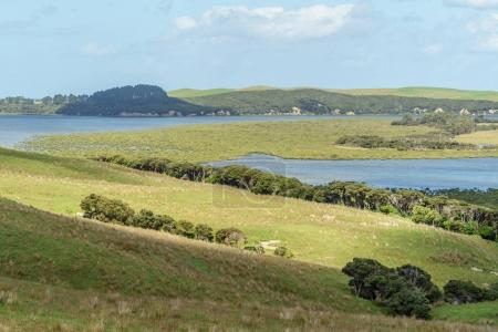 Photo for Green fields with lake and seashore, Spirits Bay, New Zealand - Royalty Free Image