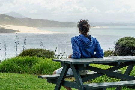 Photo pour Vue arrière de l'homme assis sur un banc et regardant l'océan, Omapere, Nouvelle-Zélande - image libre de droit