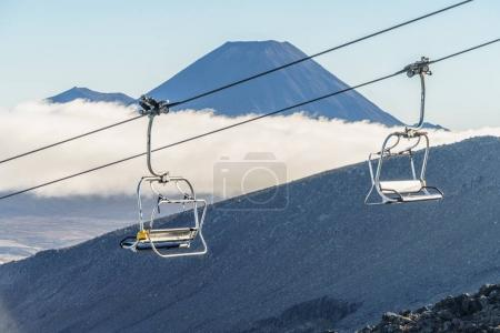Photo for Chairlift on rocky mountain with volcano on background, Mount Ngauruhoe, Tongariro National Park, New Zealand - Royalty Free Image