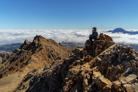 Photo pour Female hiker sitting on peak rocky mountain, Tongariro National Park, New Zealand - image libre de droit
