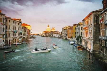 Photo for View from the Ponte dell'Accademia on boats and gondolas on the grand canal in venice on a cloudy day during glowing sunset - Royalty Free Image