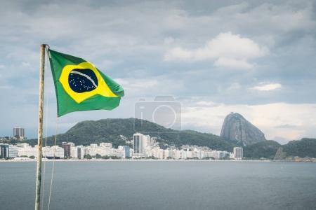 Photo pour Drapeau brésilien sur un poteau agitant contre Copacabana, Rio de Janeiro, Brésil arrière-plan avec l'emblématique montagne du pain de sucre - image libre de droit
