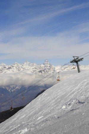 Photo pour Vue panoramique de la piste de ski large et damée dans la station de Pila dans la Vallée d'Aoste, Italie pendant l'hiver. Vers le nord se trouve la Suisse et son emblématique Cervin - image libre de droit