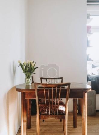 Photo pour Bouquet de fleurs sur une table en bois dans un salon minimaliste vintage lumineux - image libre de droit