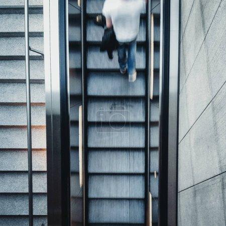 Photo pour Découvre d'en haut sur le rapide mouvement jeune homme marche dans un escalier escalier avec blue jeans et une chemise blanche ayant son pull-over saisit sous son bras - image libre de droit