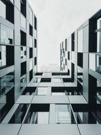 Blick in den Himmel in einer Stadt vor einem modernen Gebäude mit geometrischen Formen und vielen spiegelnden Fenstern