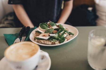 Photo for Fresh healthy vegetarian sandwich with lots of vegetables and goat cheese and an empty cup of coffee on a vintage table inside a hipster restaurant with a blurry woman in the background - Royalty Free Image