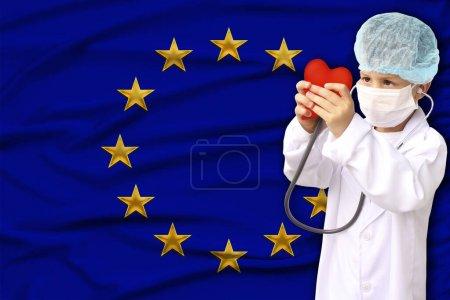 Photo pour Enfant en manteau de médecin blanc, chapeau et masque attaché un stéthoscope à un modèle de coeur rouge, recherche innovatrice, gros plan, concentration sur le visage, concept médical, cardiologie, espace de copie - image libre de droit