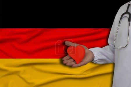 Photo pour Photo d'un médecin avec un stéthoscope avec un cœur dans la main sur le fond du drapeau national de l'Allemagne, concept de soins de santé, cardiologie, assurance maladie - image libre de droit