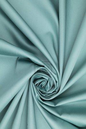 Foto de La tela de satén azul se pone sobre la mesa en una vista en espiral. Tipos blandos de drenaje - Imagen libre de derechos