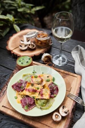 Photo pour Composition rustique : raviolis colorés aux champignons sur une table en bois avec un verre de vin blanc - image libre de droit