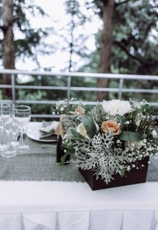 Beautifully decorated wedding table in European style with flowers, greens and cutlery