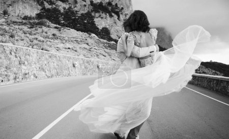 groom circling in the dance bride in the arms, stylish wedding couple, newlyweds walking along a mountain road against a beautiful view