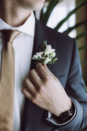 morning groom before the wedding groom puts on flower buttonhole