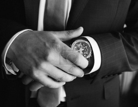 morning groom before the wedding or stylish man businessman puts a watch on his hand