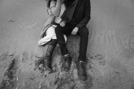 young stylish couple, in Scandinavian style sitting on sand on beach