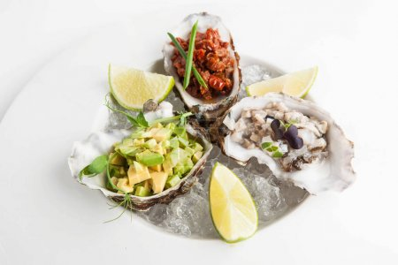 Photo for Restaurant luxury appetizer of oysters, avocado and sun-dried tomatoes on a plate with ice - Royalty Free Image