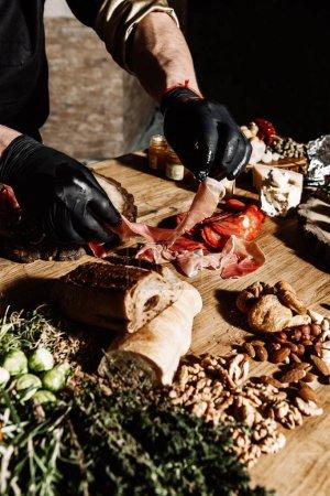 Hände des Kochs in schwarzer Schürze bereiten eine Reihe von Fleischdelikatessen zu, Marmelade, Würstchen